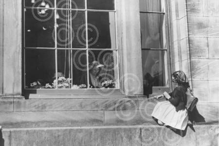 A young child sits on a window ledge trying to see a yo