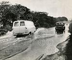 15. Cars struggle through the water on a flooded Baldov